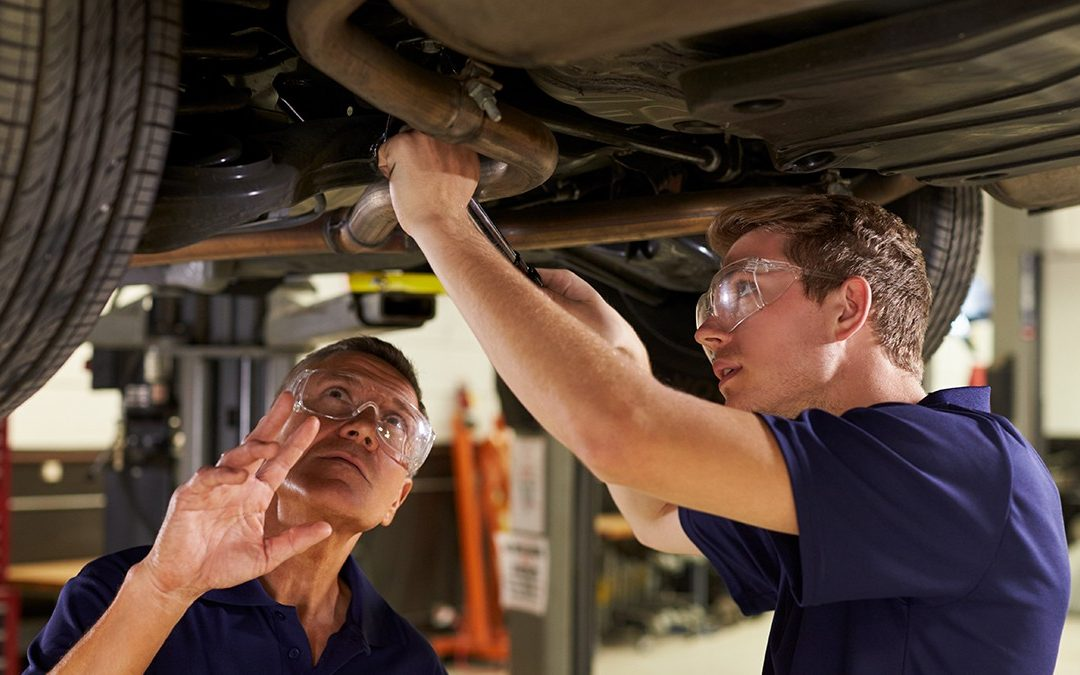un mécanicien et son apprenti travaillent ensemble sous un véhicule surélevé.