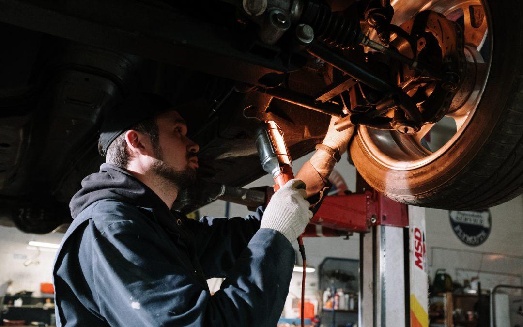 Jeune mécanicien inspectant un essieu de voiture